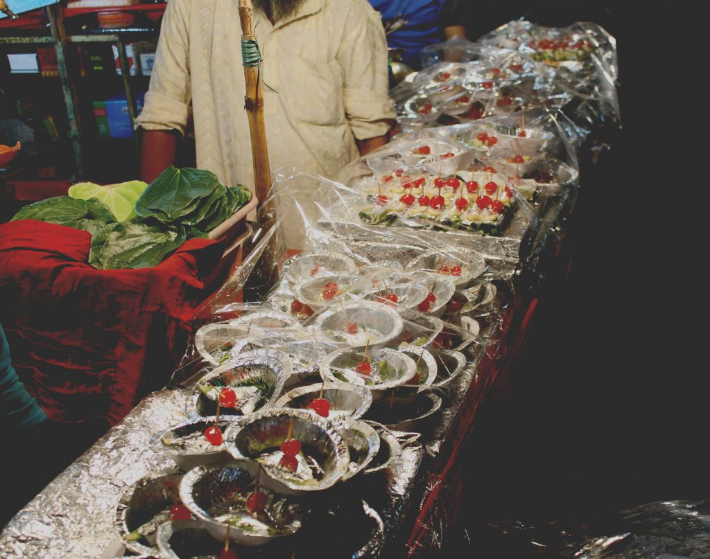 A picture of paan shop selling sweet and juicy paan ready to be chewed after dinner.