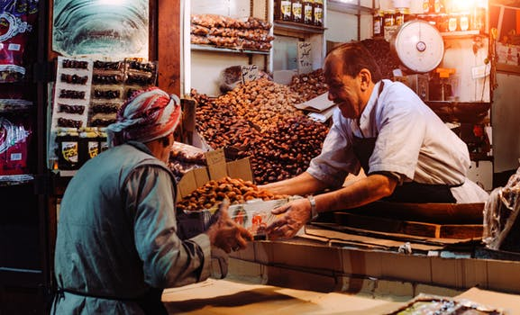 Picture of a man buying date fruits.