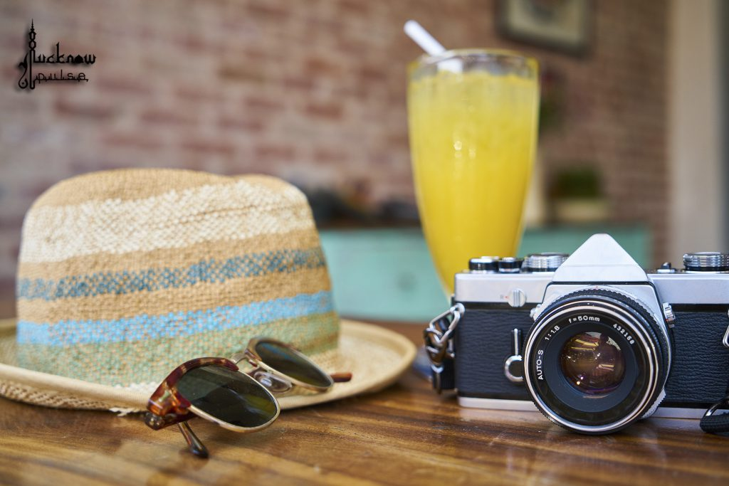 A representative pic posted by Lucknow Pulse showing a camera, sun glasses, a hat and a glass of juice... hinting of summer vacations