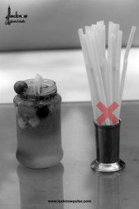 A jar full of lemonade and a box of straws. Avoid straws. Save environment